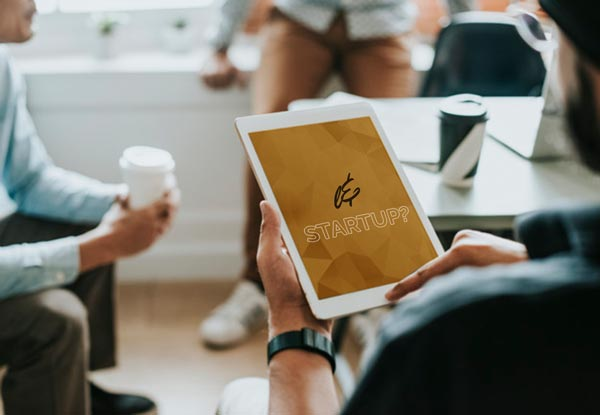 Junger Unternehmer hält einen IPad in der Hand während einer Besprechung