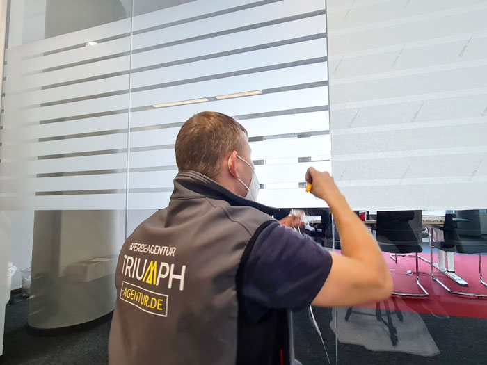 Montage der Milchglasfolie in einem Büro - gestreifte Sichtschutzfolie wird geschnitten